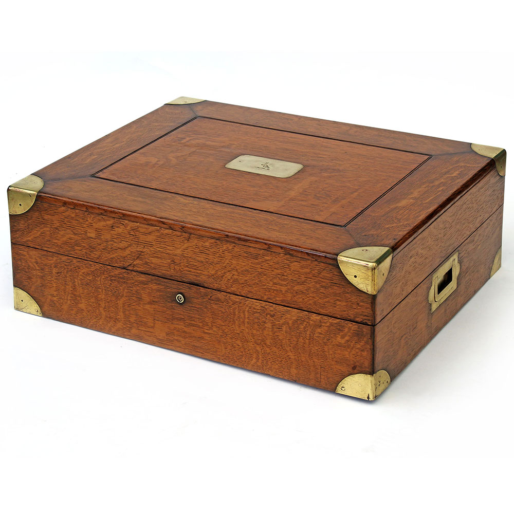 arge antique brass mounted polished oak campaign box with inset crested plate and flush mounted carrying handles. Circa 1880.