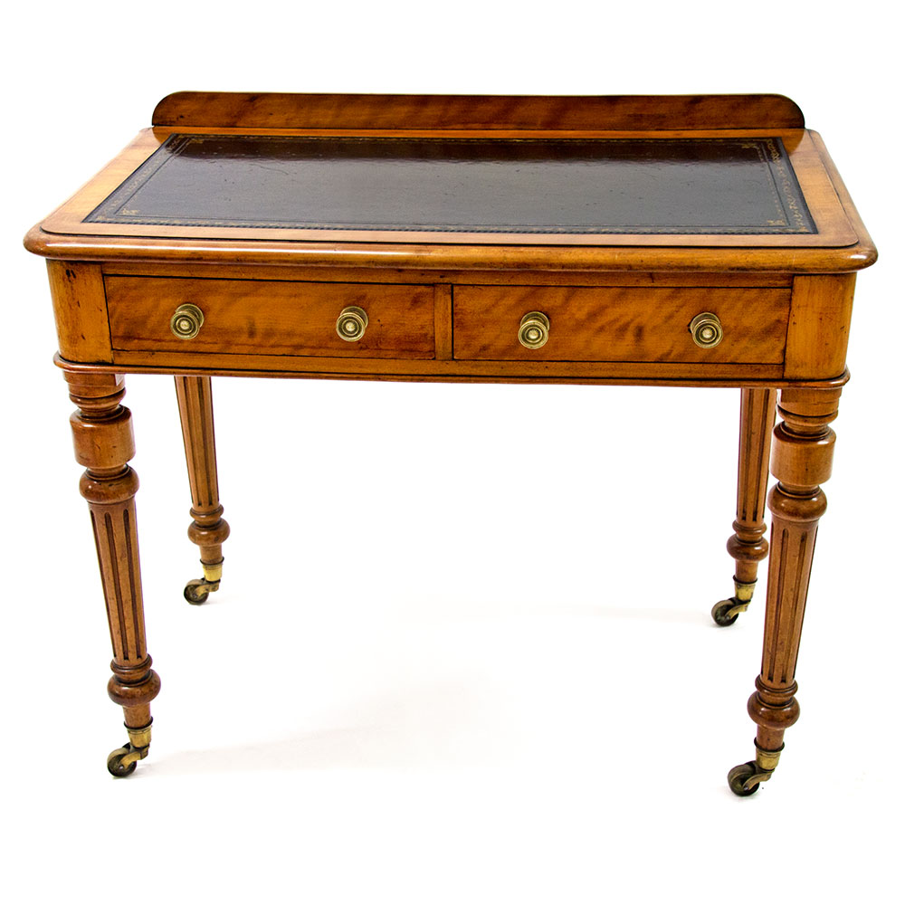 Antique satin birch two drawer writing table by J Shoolbred (stamped) reeded legs with all brass casters inset leather lining. (c.1890)