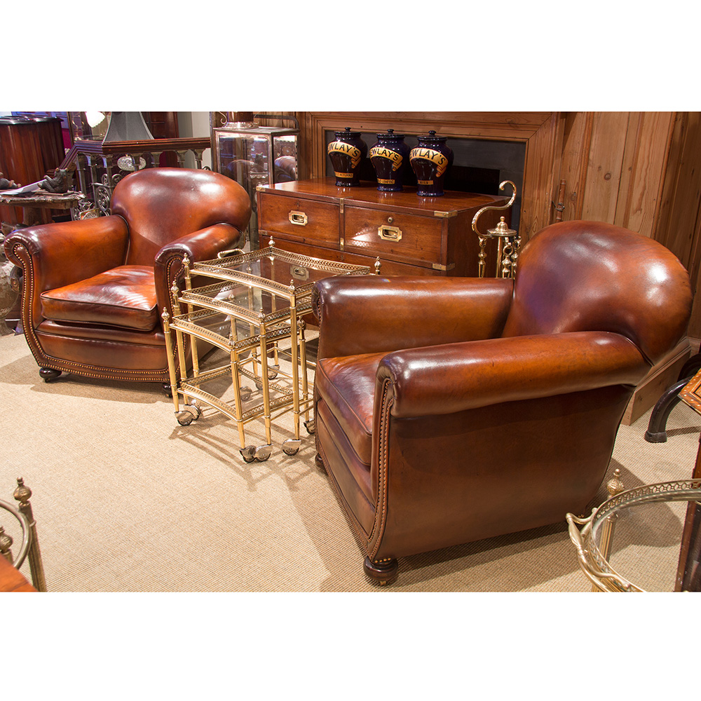 Pair of brass studded leather club chairs with cushions on turned mahogany feet with castors. Circa 1920.