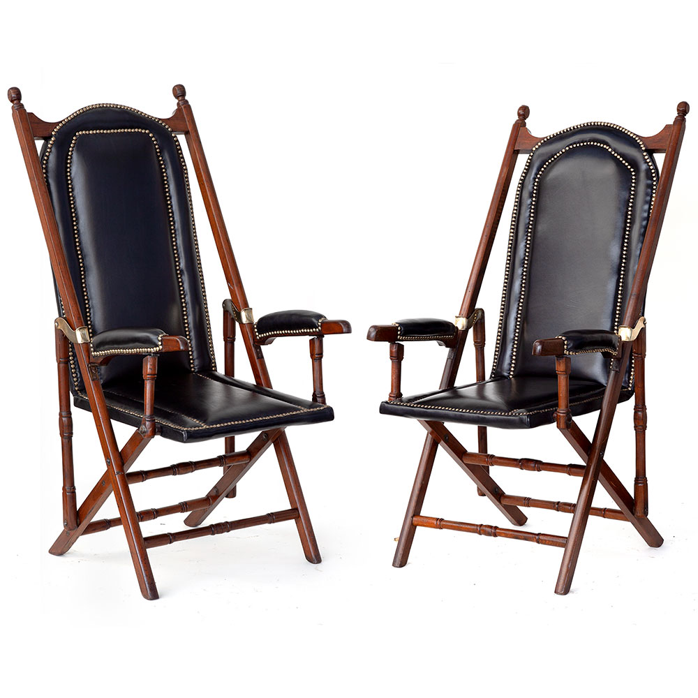 Antique matched pair of folding teak and black leather steamer chairs. (c.1900)