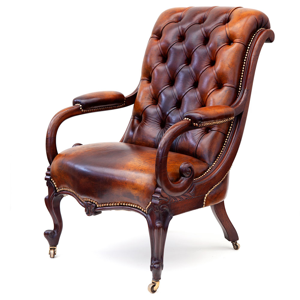 Antique mahogany framed deep buttoned leather gentelmans library swept back armchair with cabriole legs and original brass castors. (c.1880)